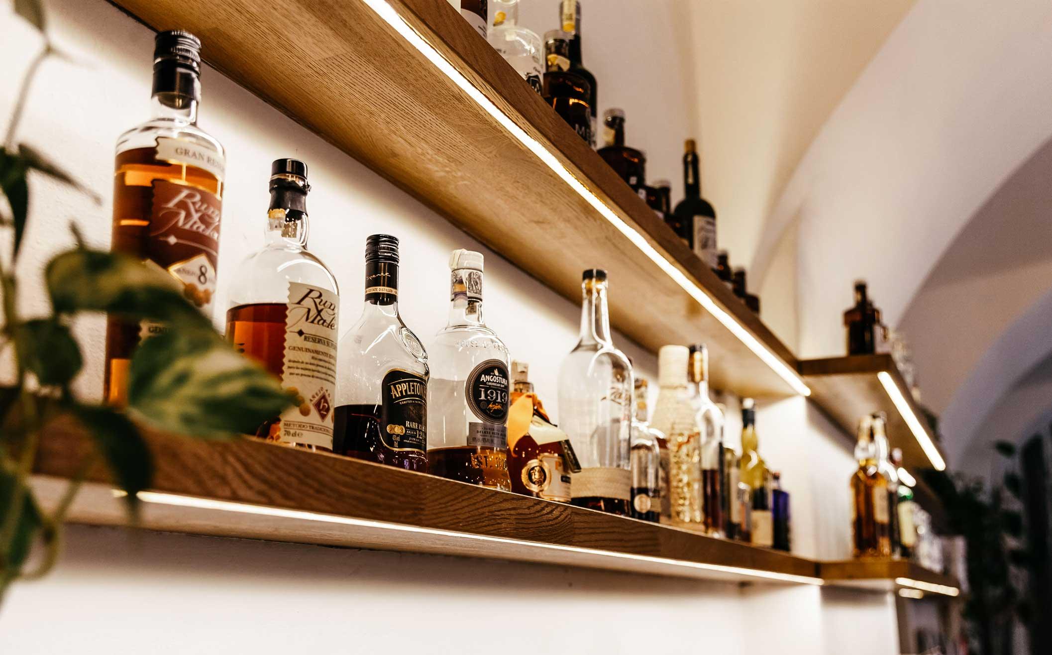Kavárna Café Datel - police za kávovým a barovým pultem. Autor: Kurz architekti