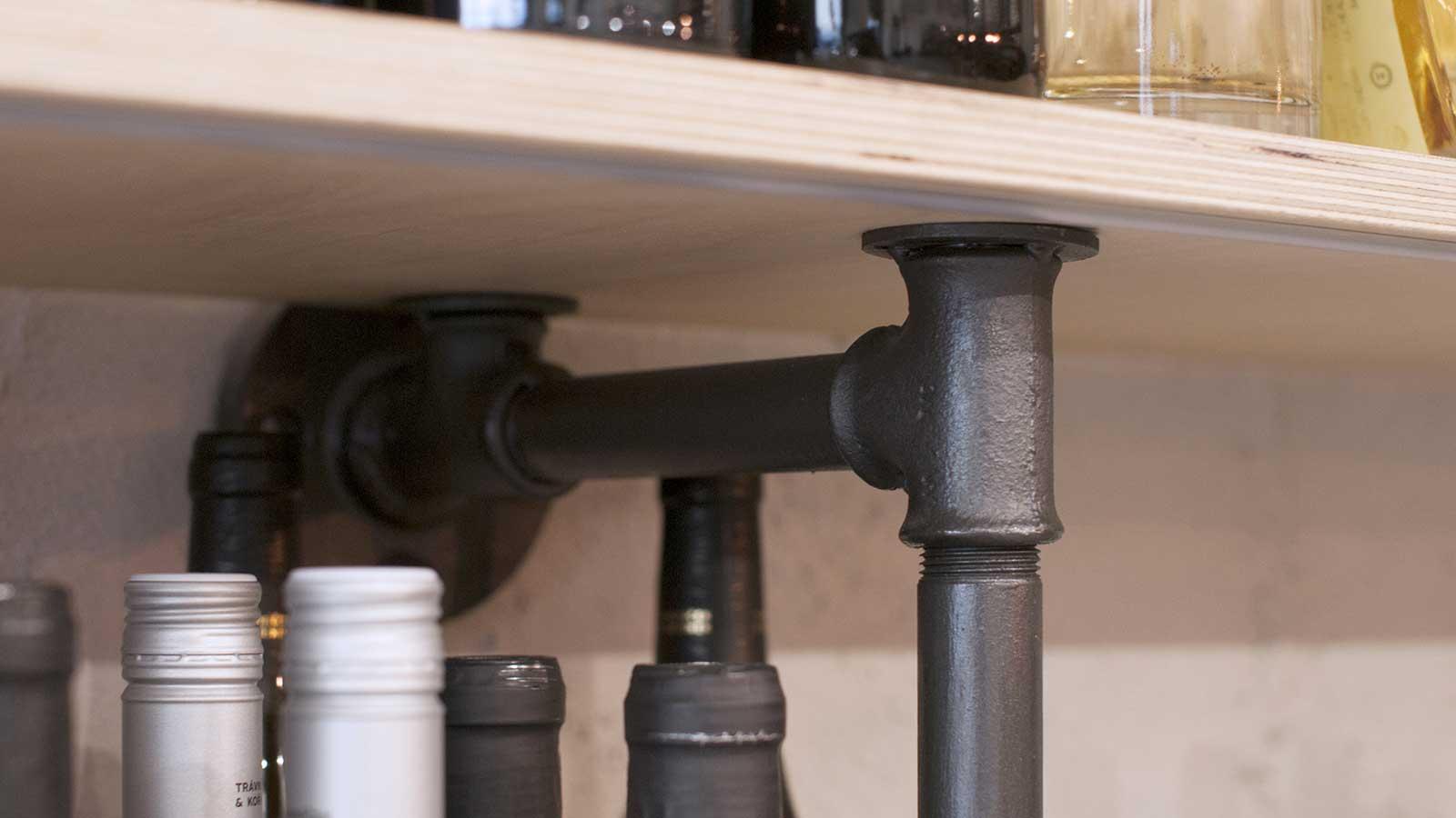 Prodejna Alkohol.cz - detailní pohled policový systém výstavních regalů, jehož kostru tvoří kovové potrubí. Autor: Kurz architekti