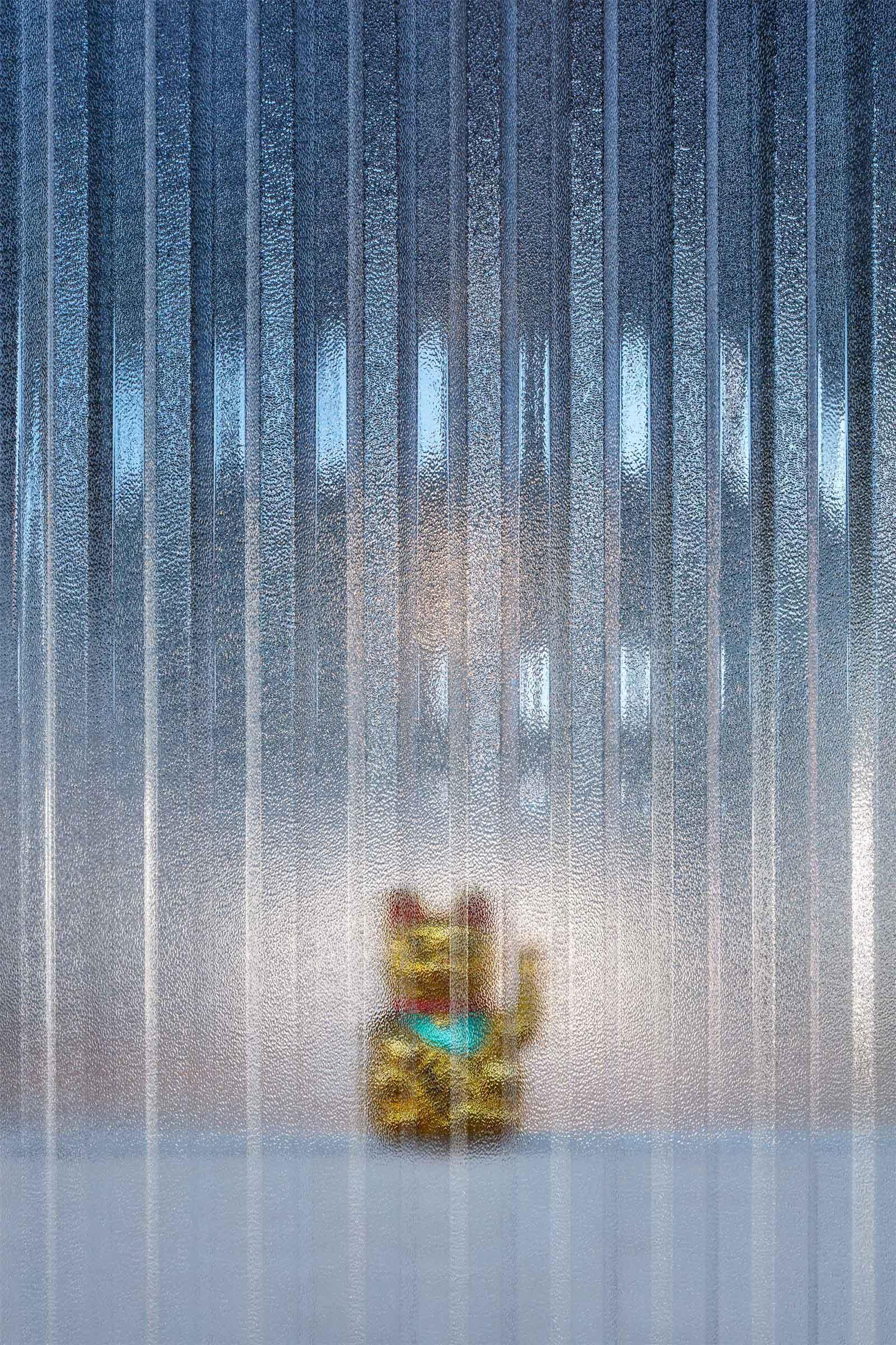 Kanceláře Sinnerschrader Praha - Maneki Neko umístěná za trapézovou polykarbonátovou stěnou meetign boxu. Maneki neko má svému majiteli přinášet štěstí a bohatství. Autor: Kurz architekti
