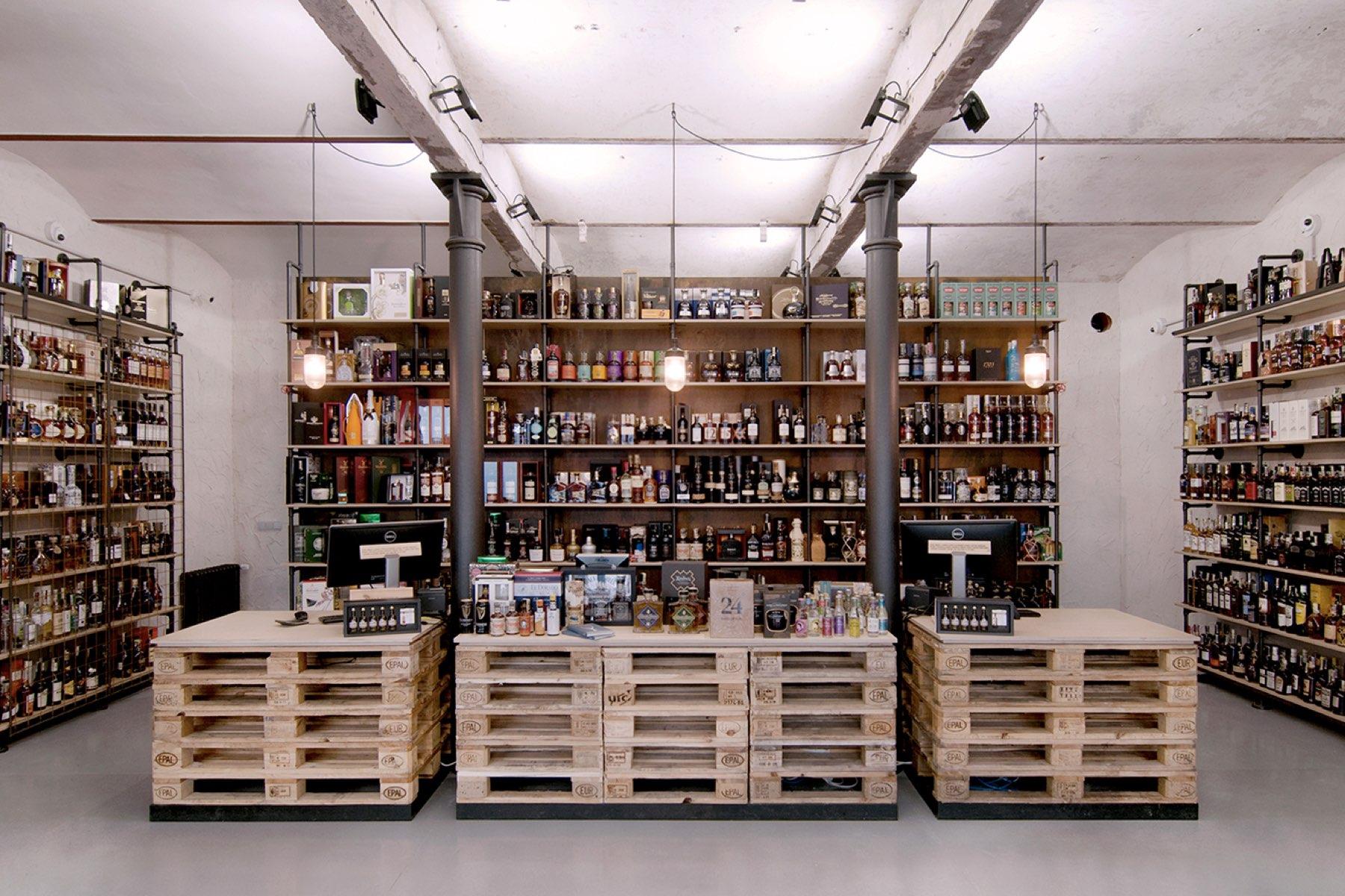 Prodejna Alkohol.cz - pohled do hotového interiéru prostoru s prodejním pultem i policovým systémem na míru. Autor: Kurz architekti